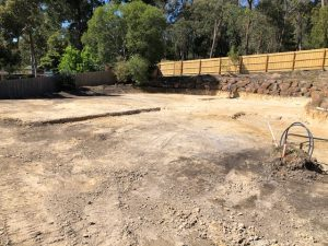 Site Cut with existing rock retaining wall around the outside