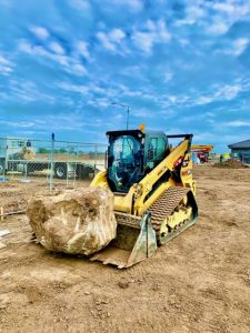 Track loader removing a large rock